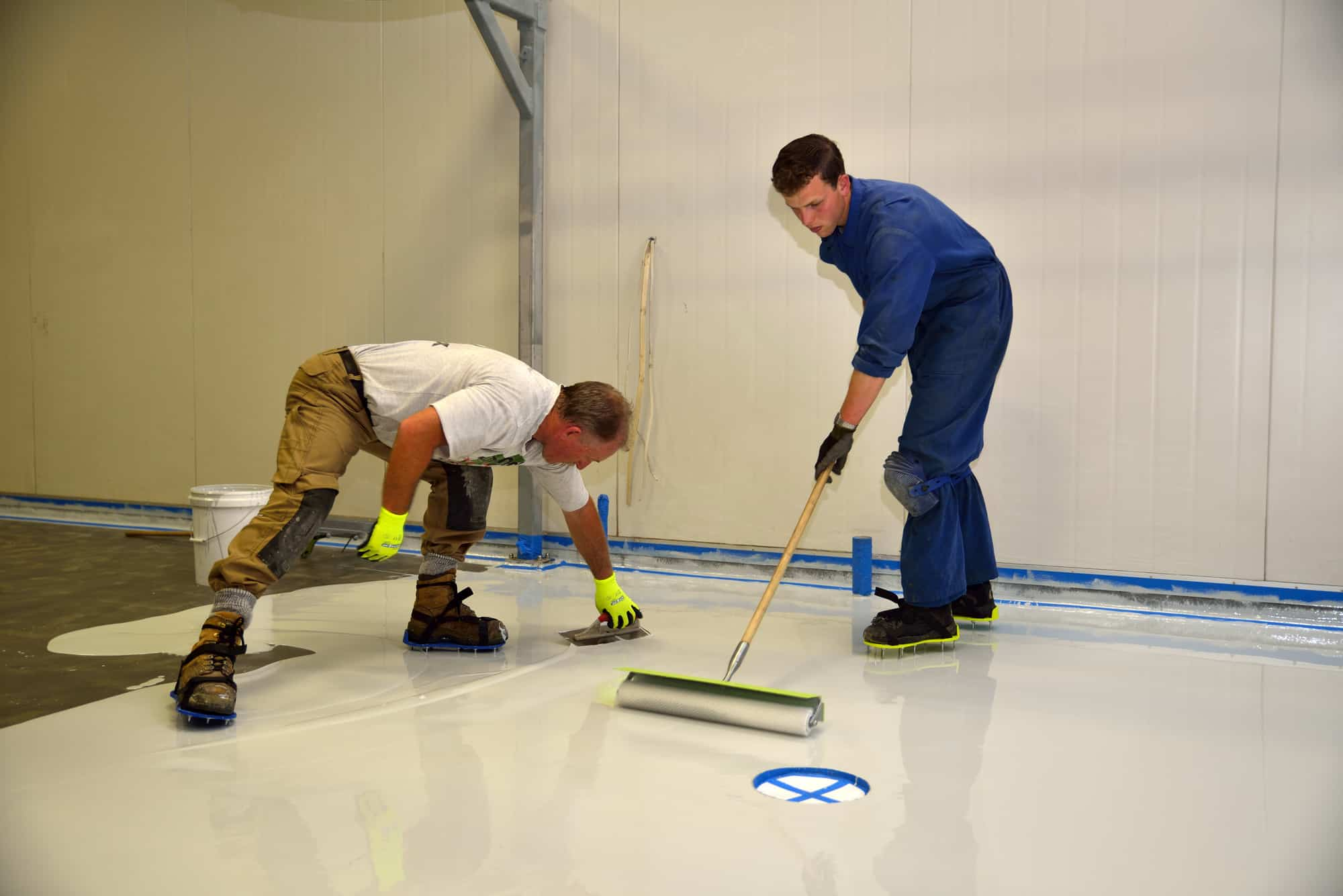 2 workmen applying a white epoxy to an industrial floor